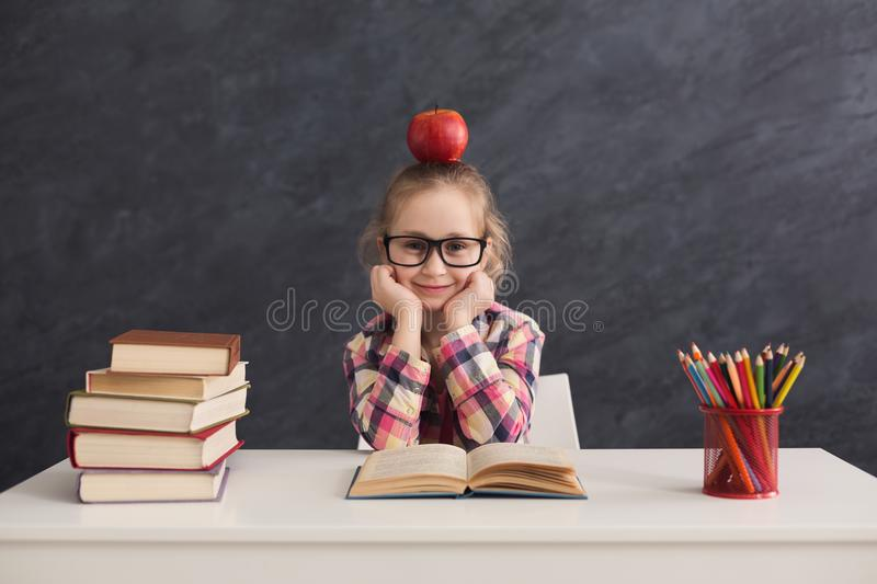 Cute girl sitting with books at table royalty free stock image