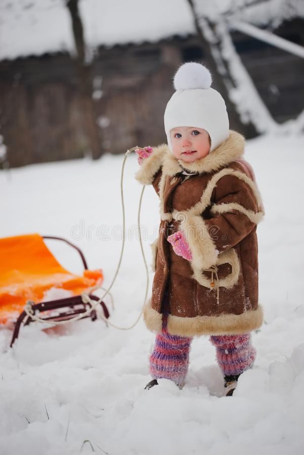 Cute girl with sled in snow. Little cute girl with sled in snow stock image
