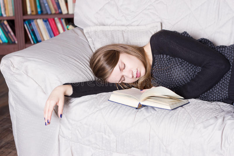 Cute girl sleeping while holding a book lying royalty free stock photos