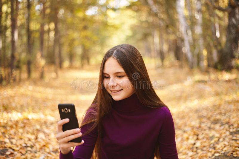 Cute girl with a smartphone in the autumn forest. royalty free stock image