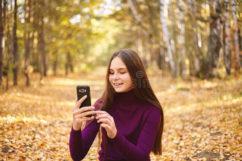 Cute girl with a smartphone in the autumn forest. stock photography