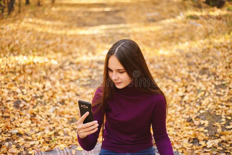 Cute girl with a smartphone in the autumn forest. stock images