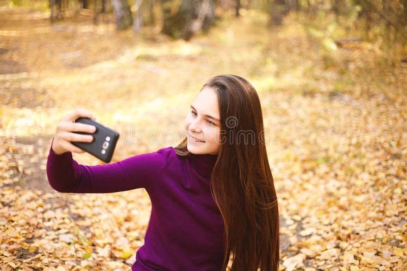 Cute girl with a smartphone in the autumn forest. royalty free stock photo