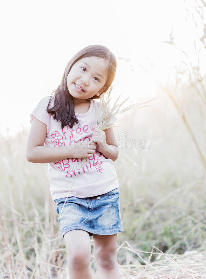 Cute girl smile and flower grass in hand. Cute girl smile and flower grass in hand with sunlight and vintage tone royalty free stock photo