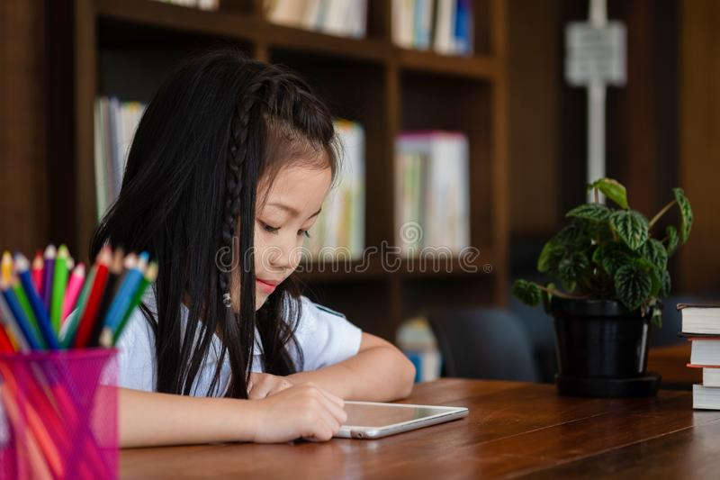 Cute girl smile sitdown and playing tablet smartphone in the lib royalty free stock images