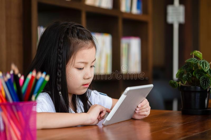 Cute girl smile sitdown and playing tablet smartphone in the lib stock images