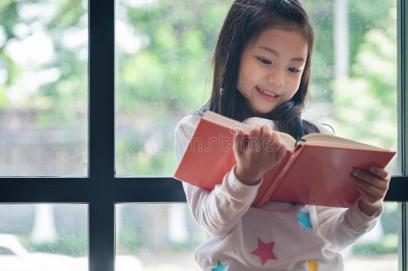 Cute girl smiled and standing reading book in the library, child royalty free stock photo