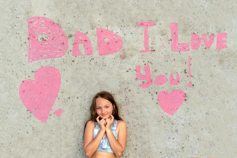 Cute girl smiling on the background of the wall with the words Dad I love you. Concept of happy father day stock image