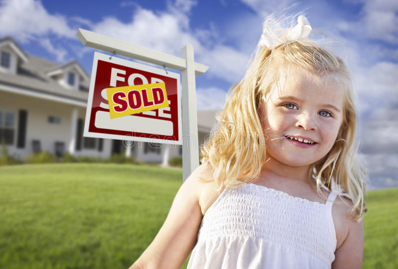 Cute Girl Sold Real Estate Sign, House. Cute Smiling Girl in Front Yard with Sold For Sale Real Estate Sign and House stock photo