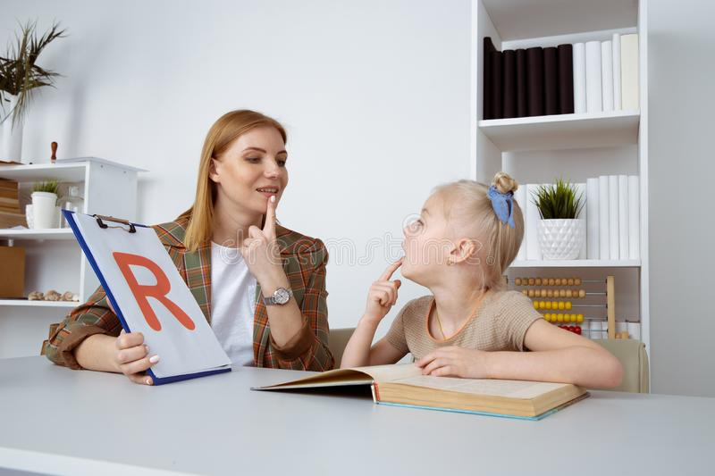 Cute girl with speech therapist in cabinet trainiing pronunciation. stock photo