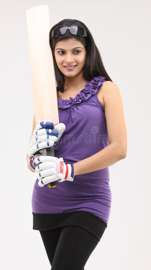 Cute girl standing with cricket bat royalty free stock photography