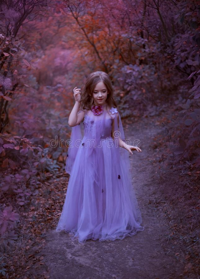 Cute girl is standing in the forest in a purple light long dress with flowers, a little princess like in a dream, walks stock photo