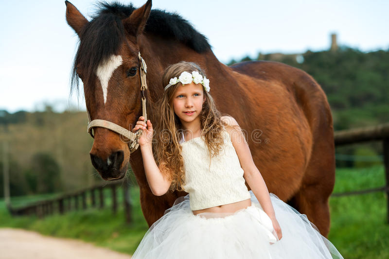 Cute girl standing next to horse. Portrait of cute girl wearing flower crown standing next to horse outdoors stock photo