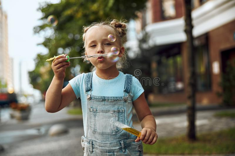 Calm little girl blowing soap bubbles stock photo royalty free stock image