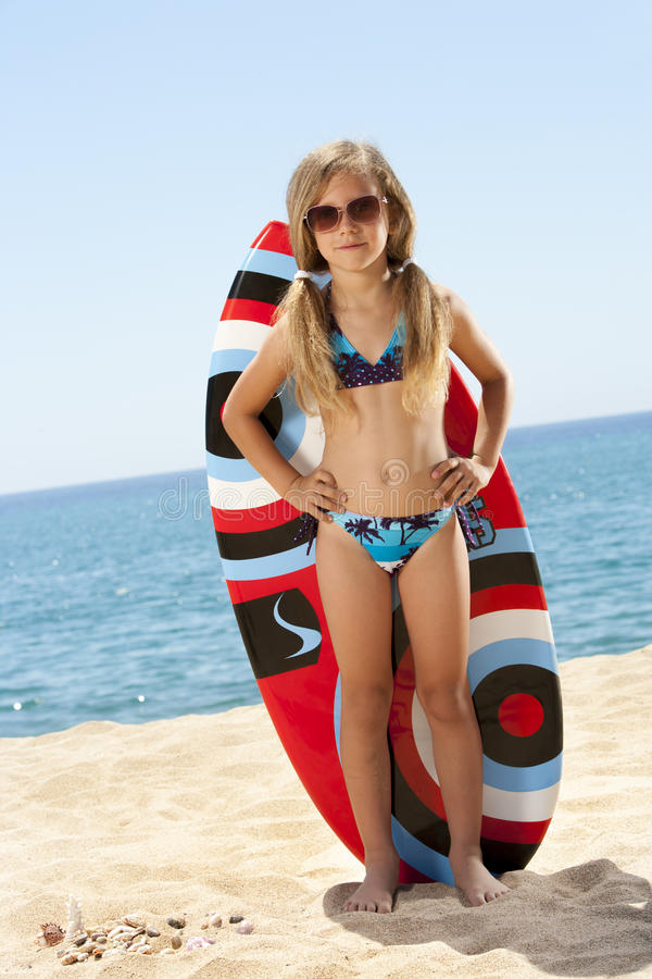 Cute girl standing with surfboard on beach. royalty free stock photo