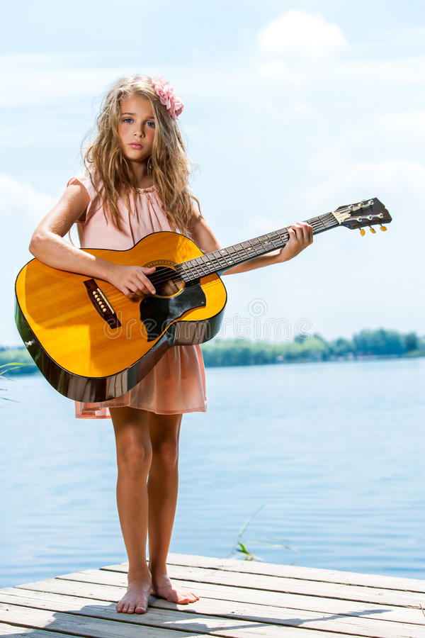 Free Cute Girl Standing With Guitar At Lake. Royalty Free Stock Photography - 34302427