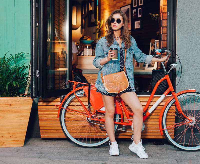 Cute girl in a summer dress, denim jacket, sunglasses and bag stands with red vintage bicycle in LA city, California. Sunny summer. On background surf cafe stock images