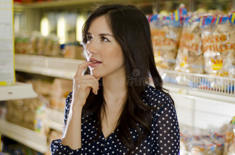 Cute girl at the supermarket. Young beautiful woman trying to decide what to buy at the grocery store stock photos