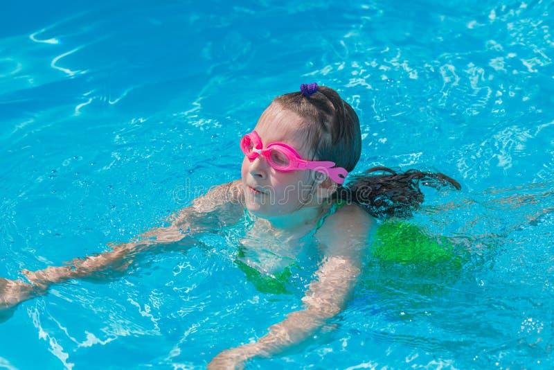 Cute girl swim in the pool stock photos