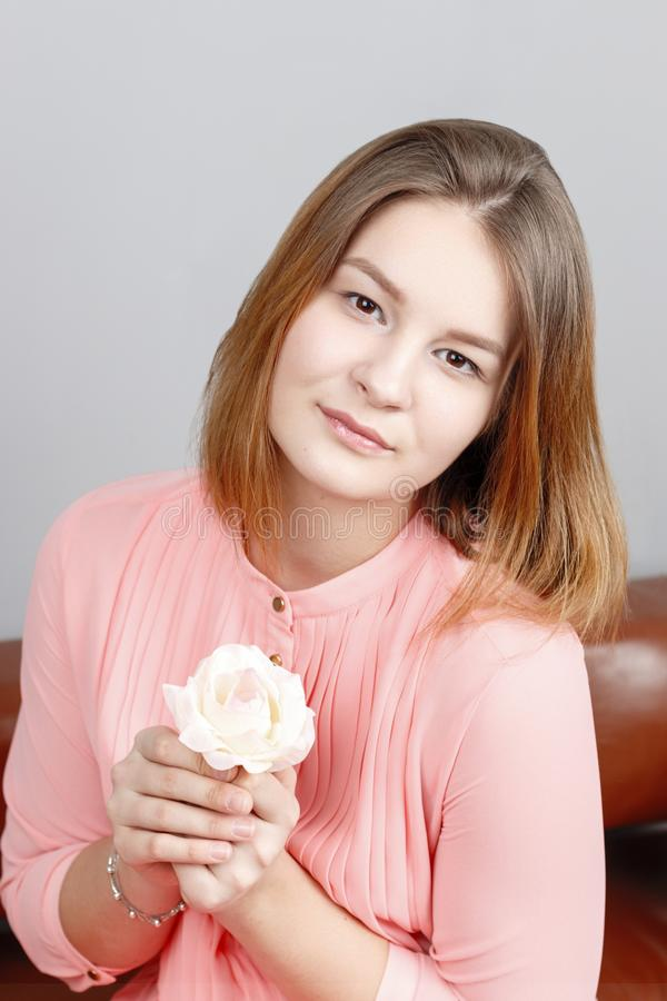 Cute girl teenager in pink dress sits with white rose stock photo