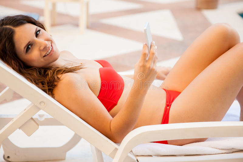 Cute girl texting by the pool royalty free stock photography