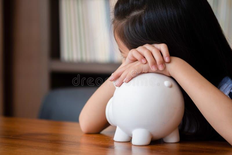 Cute girl tired sleep on piggy bank,saving money concept royalty free stock photo