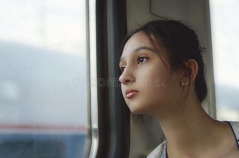 A cute girl travels by train and looks out the window. royalty free stock photography
