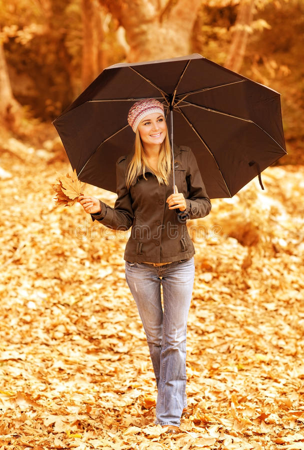 Cute girl with umbrella. Photo of cute girl walk with stylish black umbrella in the autumn park, pretty woman walking outdoors in rainy weather and holding stock image