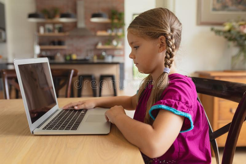 Cute girl using laptop on dining table in a comfortable home stock photo