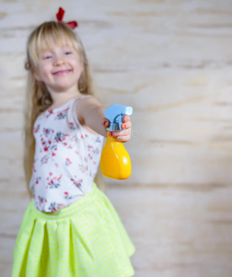 Cute girl using spray bottle stock photo