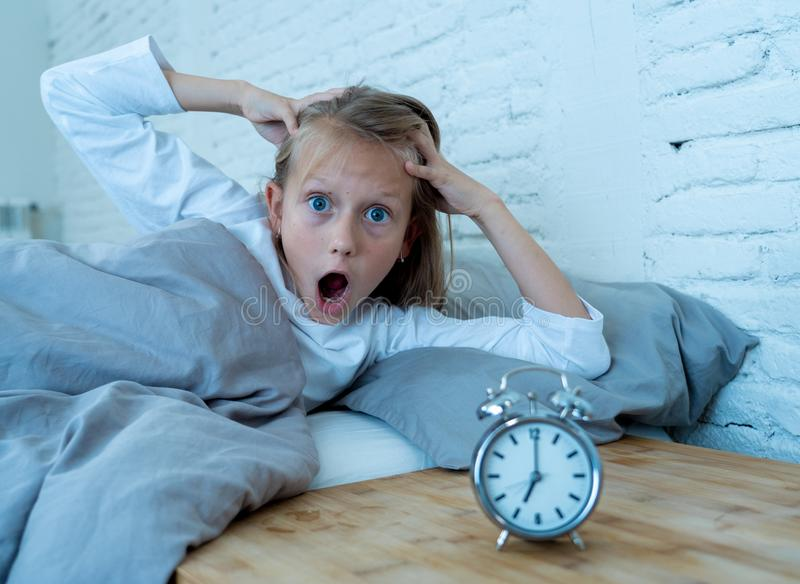 Cute girl waking with alarm clock feeling tired and angry time to go to school early in the morning royalty free stock images