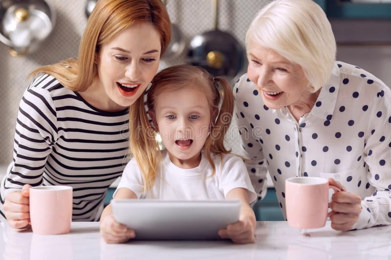 Cute girl watching cartoon on tablet with mother and grandmother stock image