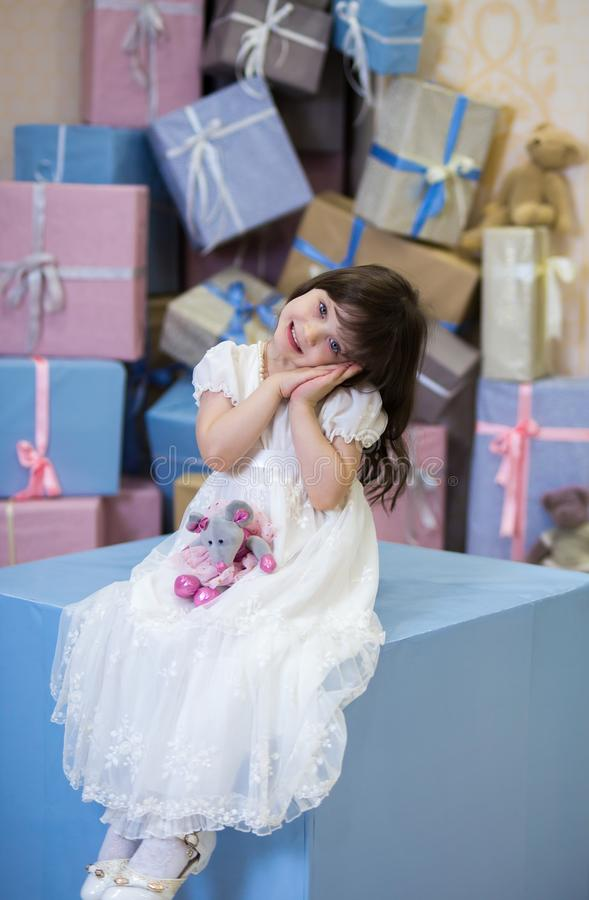 Cute girl with wavy hair in a white vintage dress is smiling, her arms are folded together under her cheek, she is holding a toy stock images