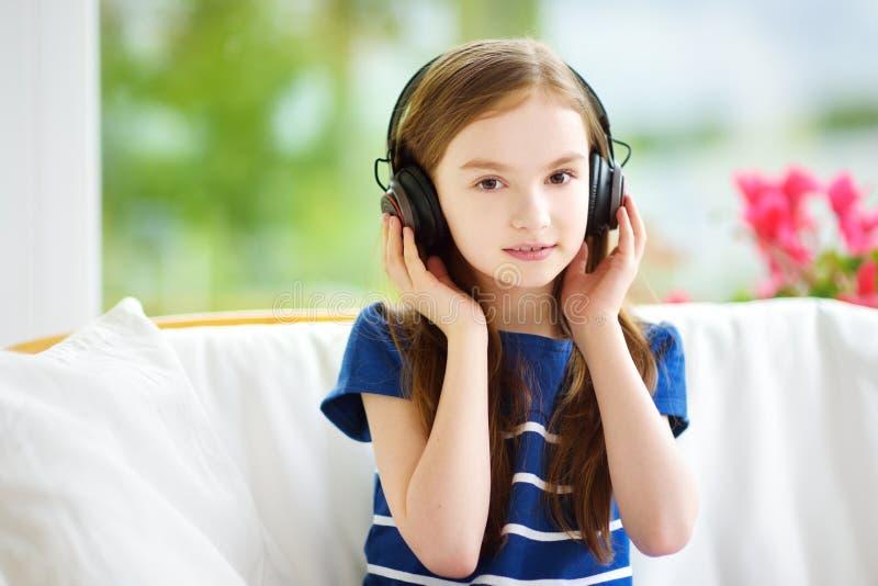 Cute girl wearing huge wireless headphones. Pretty child listening to the music. Schoolgirl having fun listening to kid`s songs at. Cute little girl wearing huge stock photos