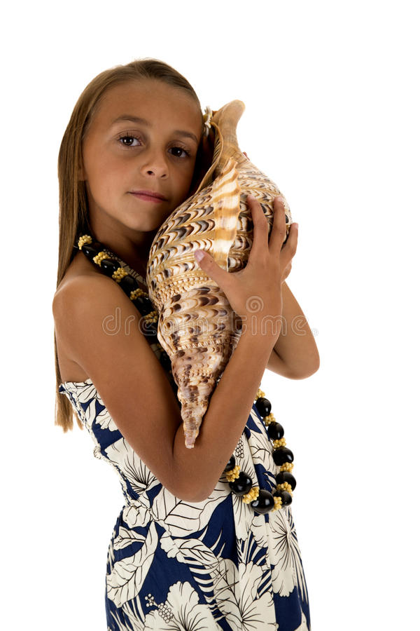 Cute girl wearing a tropical dress and holding a large seashell stock photography