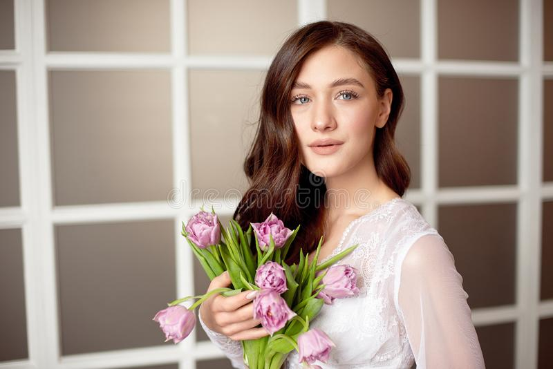 Cute girl in a white lace dress holding a bouquet of flowers of tulips in her hands a gift for a holiday to the women`s royalty free stock image