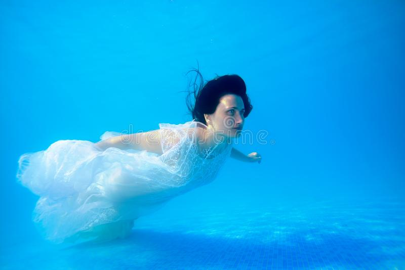A cute girl in a white wedding dress is floating underwater near the bottom of the pool on a Sunny day. Unusual wedding stock photos