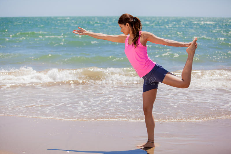 Cute girl working on her balance. Pretty Latin woman in sporty outfit doing some yoga at the beach stock image