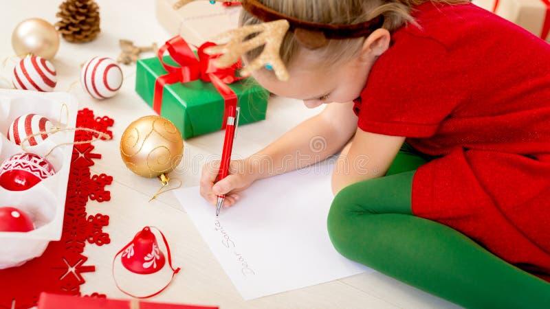 Cute girl writing letter to Santa on livingroom floor. Young girl writing her christmas wishlist. stock image