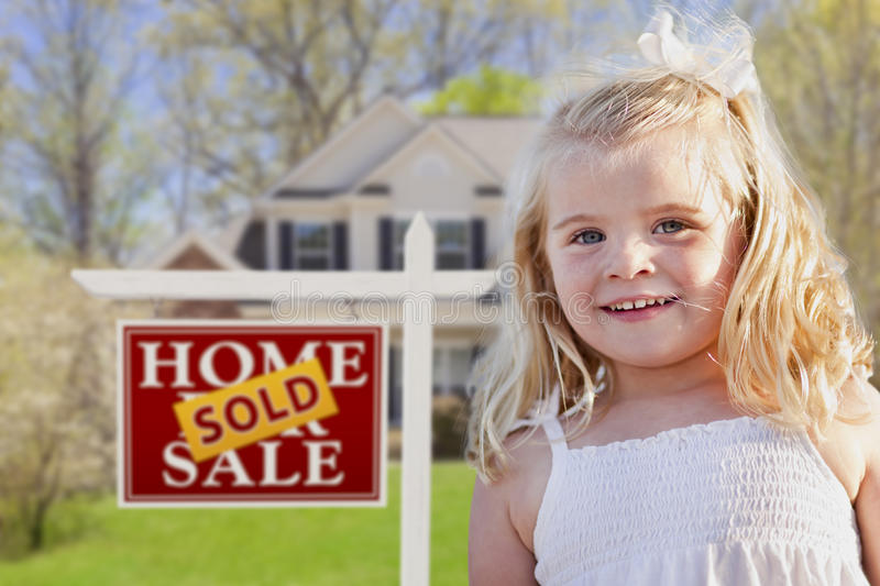 Cute Girl in Yard with Sold For Sale Real Estate Sign and House. Cute Smiling Girl in Front Yard with Sold For Sale Real Estate Sign and House royalty free stock photo