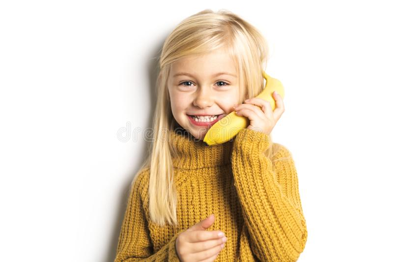 A Cute girl 5 year old posing in studio with banana fruit royalty free stock photography