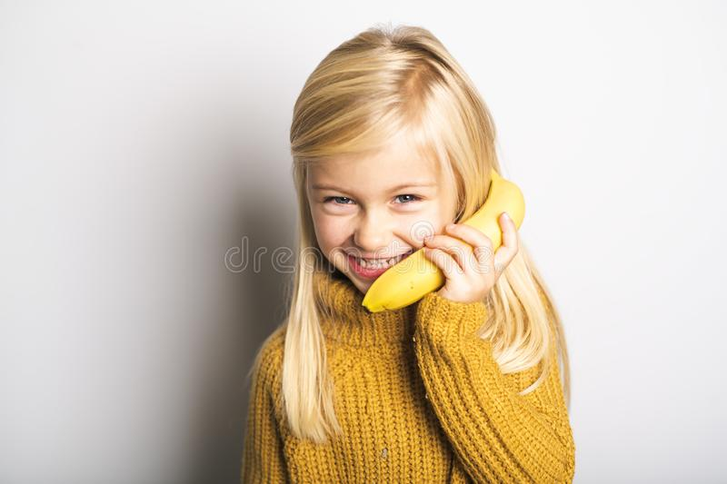A Cute girl 5 year old posing in studio with banana fruit stock photos