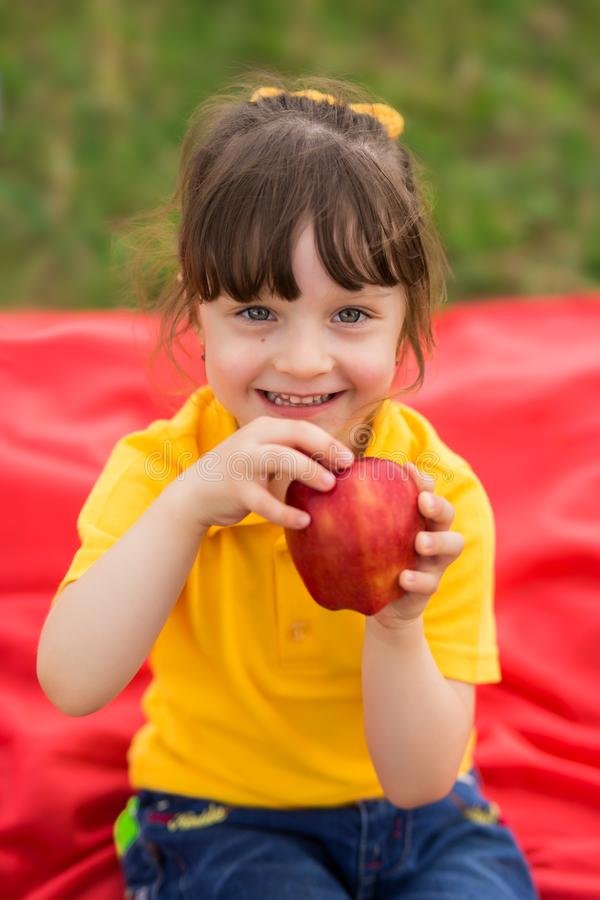 Cute girl 4 years old with a bang, in a yellow T-shirt laughs and holds a big red apple. children`s picnic in late summer - early royalty free stock image