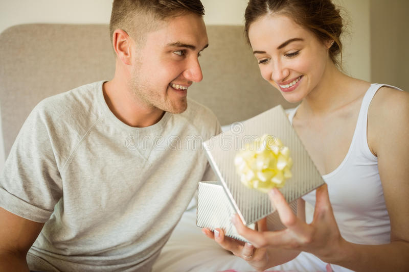 Cute girlfriend opening her gift. At home in the bedroom stock photos