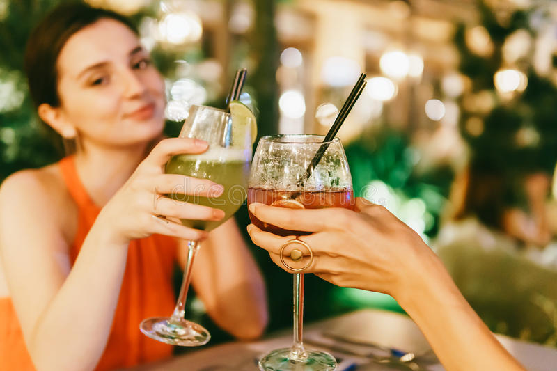 Cute Girls Celebrating Night Out With Cocktail Drinks royalty free stock photography