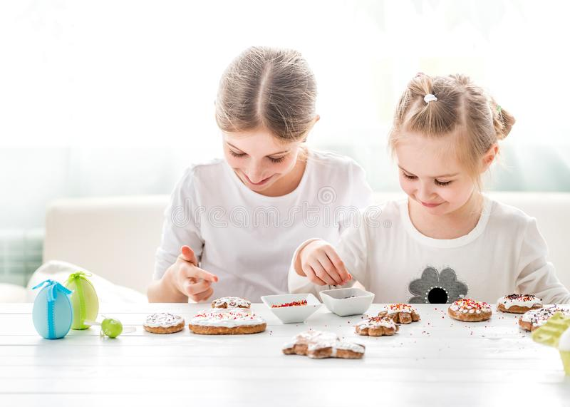 Cute girls decorating Easter cookies royalty free stock image