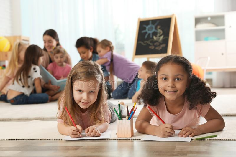 Cute girls drawing on floor while kindergarten teacher reading book to other children royalty free stock image