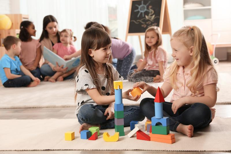 Cute girls playing with building blocks on floor while kindergarten teacher reading book to other children stock image