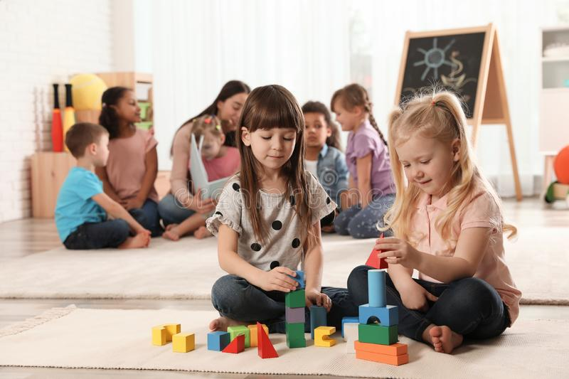 Cute girls playing with building blocks on floor while kindergarten teacher reading book to other children stock photography