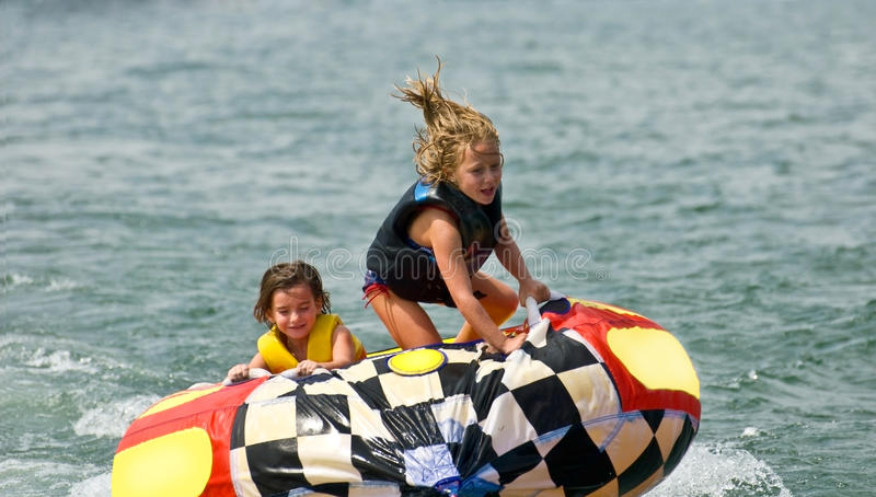 Cute Girls on Tube Behind Boat. Two brave young girls on a tube being pulled behind a boat. One hanging on for dear life, the other standing and being bounced royalty free stock image